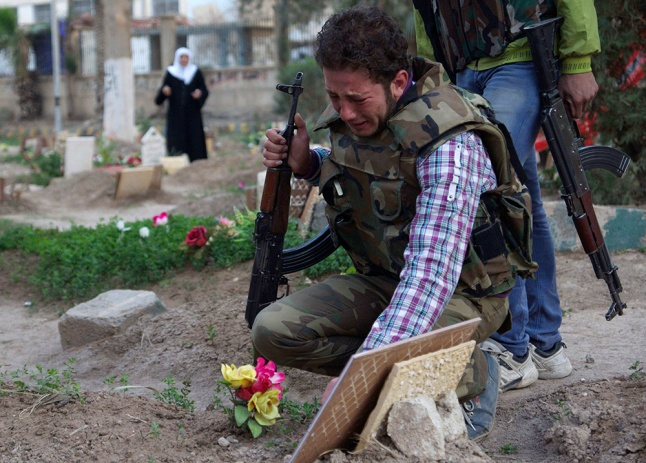 A Free Syrian Army fighter mourns at the grave of his father in a public park that has been converted into a makeshift graveyard in Deir el-Zor